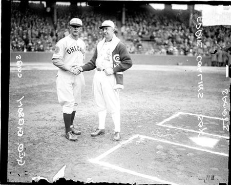 Cubs manager or player and White Sox player/manager Eddie Collins, shaking hands behind home plate on the field at Comiskey Park