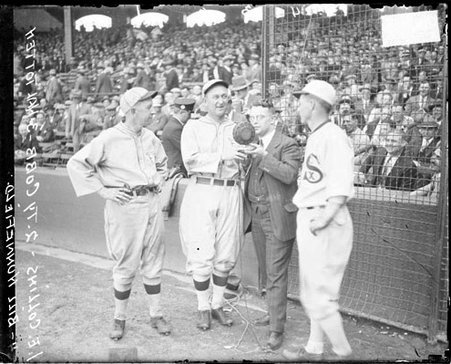 Baseball players, Eddie Collins, Ty Cobb, Bill Hunnefield, White Sox, and sportscaster, Hal Totten, of WMAQ radio with microphone in front of grandstands on the field at Comiskey Park